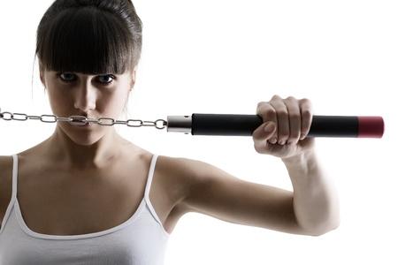 nunchaku: portrait of sport karate girl with nunchaku, fitness woman silhouette studio shot over white background