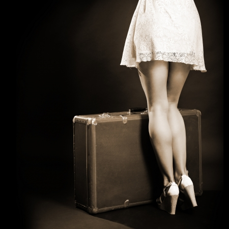 adult 80s: Travel sexy young woman hitchhiking with retro suitcase, vintage female studio portrait over black background, sepia toned
