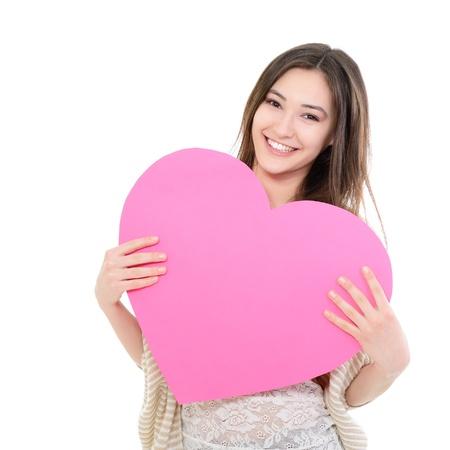 ragazza: ritratto di attraente felice sorridente ragazza adolescente con cuore rosa, amore vacanza san valentino simbolo su sfondo bianco Archivio Fotografico