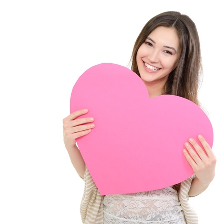 mothers day: portrait of attractive happy smiling teen girl with pink heart, love holiday valentine symbol over white background