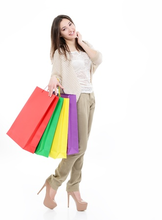 beautiful happy young woman with colored shopping bags, full lengh portrait of girl shopaholic over white photo