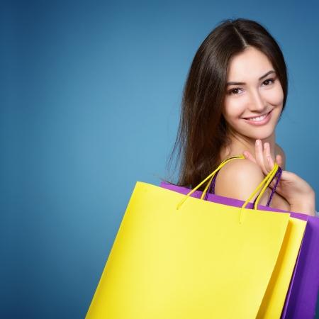 chicas comprando: joven y bella mujer con bolsas de compras de colores sobre fondo azul Foto de archivo