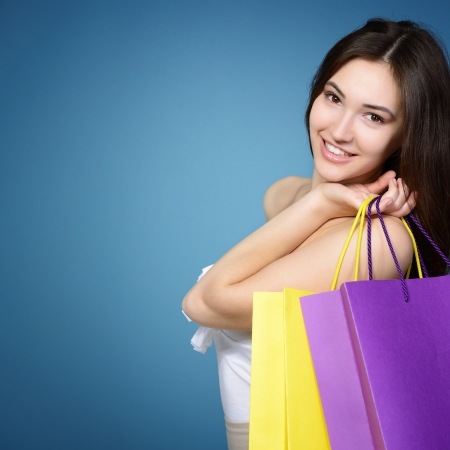beautiful teen girl with colored sale shopping bags over blue background photo