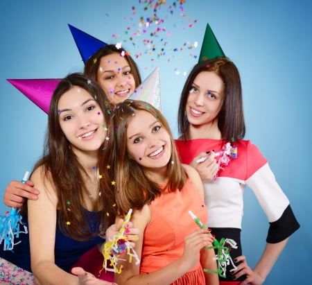 hedonistic: Joyful teen girls have fun on birthday party, over blue Stock Photo