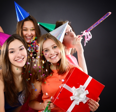 company party: Joyful happy smiling teen girls have fun on birthday party, over black