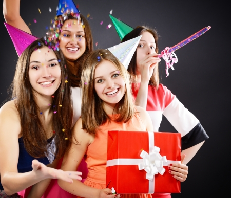 Joyful happy smiling teen girls have fun on birthday party, over black photo