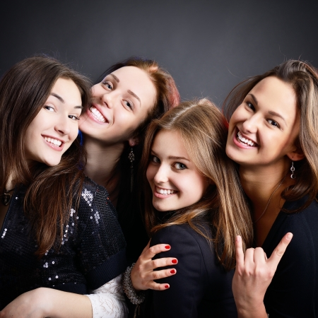 fashionable attractive happy party teen girls smiling over black background photo