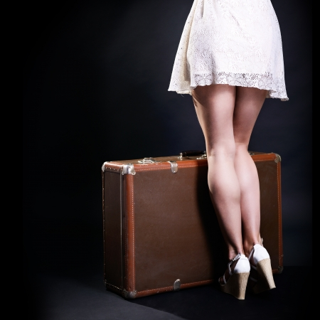 adult 80s: Travel sexy young woman hitchhiking with retro suitcase, vintage female studio portrait over black background