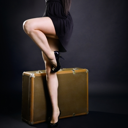 Travel sexy young woman hitchhiking with retro suitcase, vintage female studio portrait over black background photo