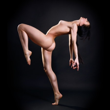 naked sexy girl: Dancing young fitness woman with perfect body, naked sexy girl with long legs and black hair. Studio shot over dark blue background.
