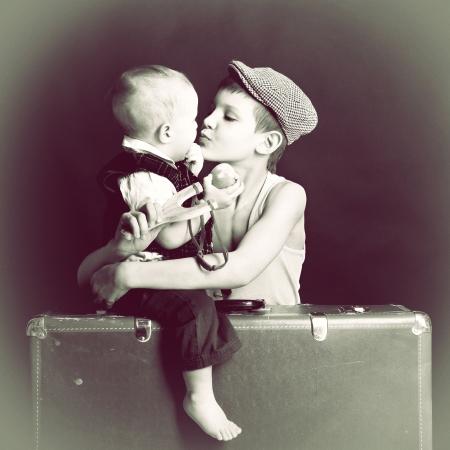 retrato del arte del vintage del niño pequeño abraza y besa a su bebé hermano apoyado en la maleta vieja, la estilización retro de 30-50s, tonos Foto de archivo - 19422014