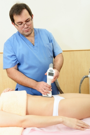 apparatus: young beautiful woman getting anticellulite and anti fat therapy in beauty salon
