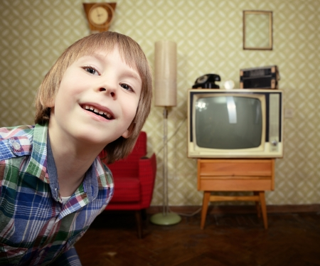 vintage art portrait of liitle boy looking out at camera in room with interior from 70s, retro stylization, toned photo