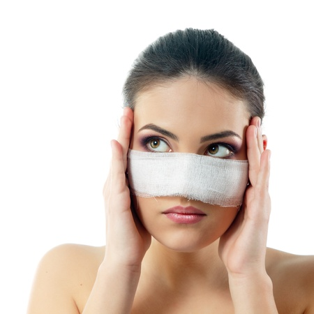 cosmetic surgery: portrait of beautiful young female face with bandage on her nose - beauty treatment plastic surgery Stock Photo
