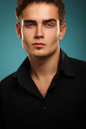 brunets: Trendy young man in black shirt, portrait of sexy fashion boy looking right over dark blue background