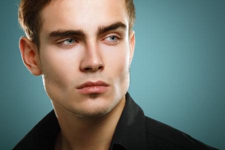 bel homme: Trendy jeune homme en chemise noire, portrait d'un gar�on de mode sexy regardant � droite sur fond bleu fonc�