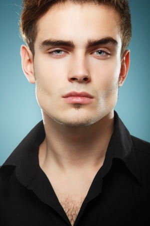 attractive man: Trendy young man in black shirt, portrait of sexy fashion boy looking right over dark blue background
