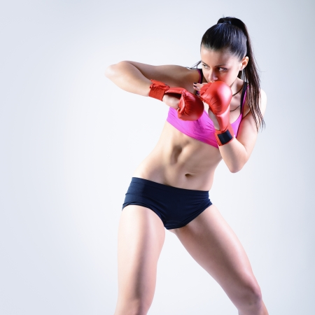 kickboxing: sport young woman with combativity gloves going to fighting, active fitness girl, studio shot