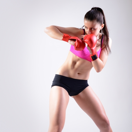 sport young woman with combativity gloves going to fighting, active fitness girl, studio shot photo