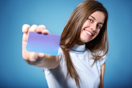 beautiful friendly smiling confident teen girl showing card in hand, over blue background photo