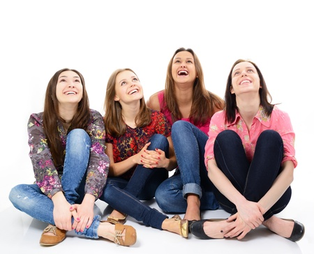 four friends: happy young women sitting together smiling and looking up, over white background Stock Photo