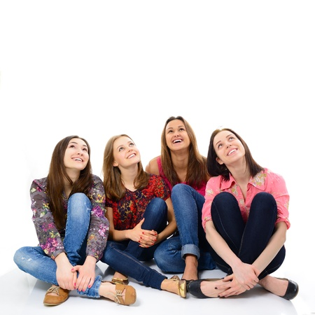 emotional woman: happy young women sitting together smiling and looking up, over white background Stock Photo
