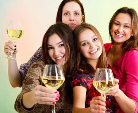 Happy young women friends touching the glasses with each other on party and have fun photo