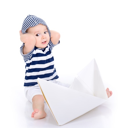 ship's boy. cute baby boy sitting in striped vest with ship of paper - sailor in future, over white background photo