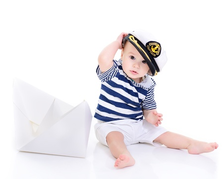 seaman: cute baby boy sitting in captain cap with ship of paper - sailor in future, over white background