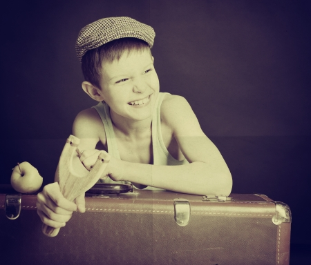 naughty boy: vintage art portrait of liitle boy looking at camera holding catapult and  leaning on old suitcase, retro stylization of 30-50s, toned