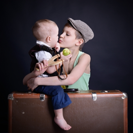 vintage art portrait of little boy hugs and kiss his baby brother leaning on old suitcase, retro stylization of 30-50s photo