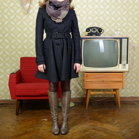art portrait of young woman standing in room with vintage wallpaper and interior with tv, phone and chair, retro stylization 60-70s photo