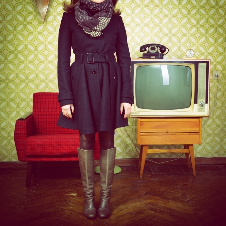 art portrait of young woman standing in room with vintage wallpaper and interior with tv, phone and chair, retro stylization 60-70s, toned photo