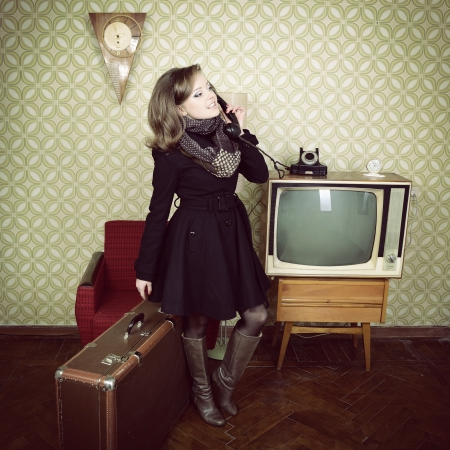 art portrait of young woman standing in room calling phone with vintage wallpaper and interior with tv, clocks, chair and suitcase, retro stylization 60-70s, toned photo