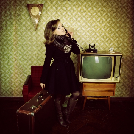 art portrait of young woman standing in room calling phone with vintage wallpaper and interior photo