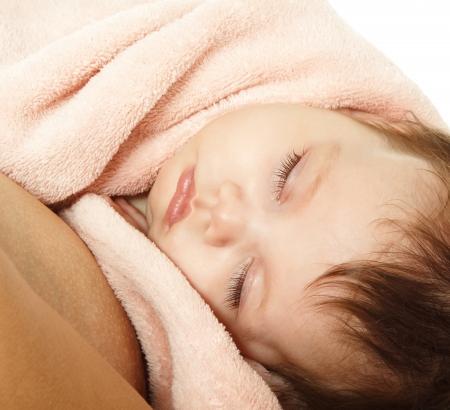 1 2 month: cute baby sleeping on mothers hands, beautiful kids face closeup, studio shot Stock Photo