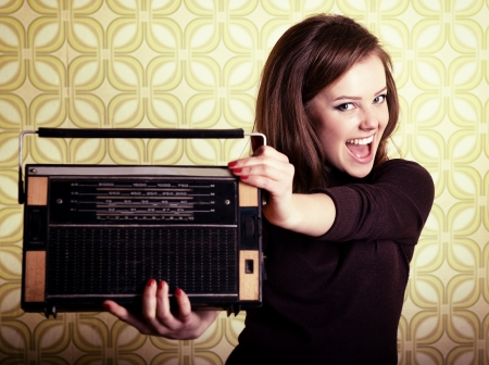 ecstatic: art portrait of young smiling ecstatic woman holding radio player in room with vintage wallpaper, retro stylization 60-70s, toned