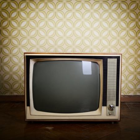 tv retro con caja de madera en la habitación con wallper época y parquet