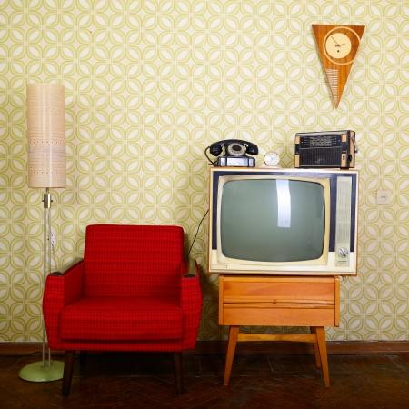 Salle vintage avec du papier peint, vieux fauteuil façonné, rétro tv, téléphone, horloges, lecteur radio et lampe standart Banque d'images - 19874117