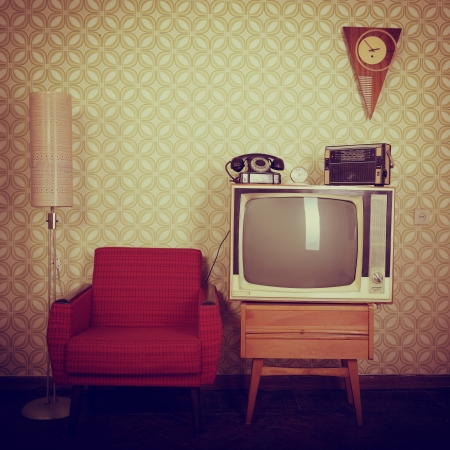 vintage furniture: Vintage room with wallpaper, old fashioned armchair, retro tv, phone, clocks, radio player and standart lamp