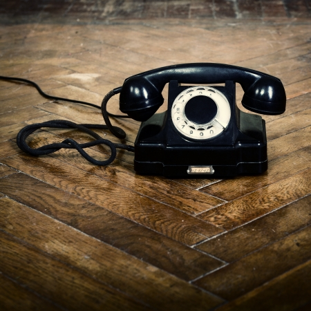 phone support: vintage old telephone, black retro phone is on the floor of used parquet