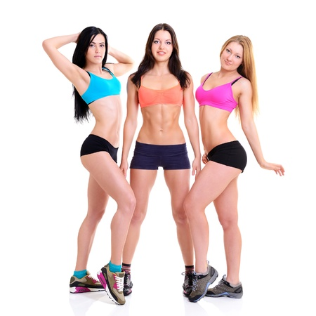 girl fitness: Three Graces - fitness girls, portrait of sport young women with perfect bodies, studio shot over white Stock Photo