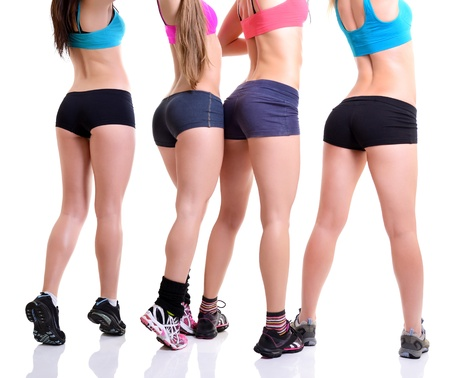 backside: legs and bottoms of fitness girls, back view of sport young women with perfect bodies, over white Stock Photo