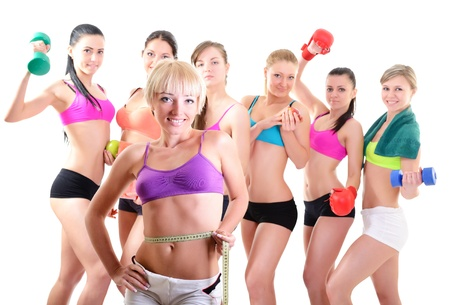 group fitness: Group of fitness girls holding measuring tape, dumbbells, scales and boxing gloves. Portrait of sport young women with perfect bodies, studio shot over white