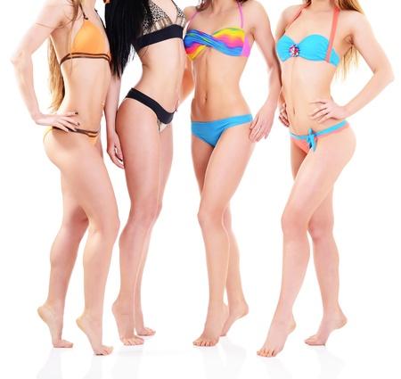 ni�as en bikini: chicas en bikini, cuatro mujeres j�venes cauc�sicos atractivas en trajes de ba�o en blanco Foto de archivo