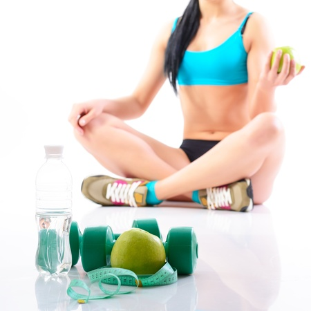 loss: Fitness woman holding an apple with water, dumbbells and measuring tape, over white background Stock Photo