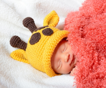 sweet smile: cute baby sleeping in funny yellow giraffe hat and smiling in sweet dreams, beautiful kids face closeup
