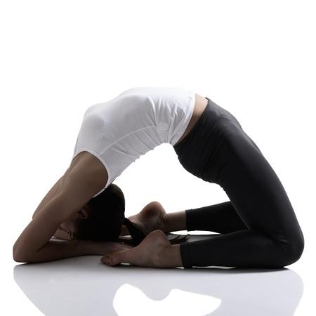 stretching: retrato de la muchacha del deporte haciendo ejercicio estiramiento de yoga, estudio de disparo en la t�cnica de la silueta sobre el fondo blanco