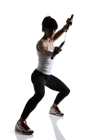sport karate girl doing exercise with nunchaku, fitness silhouette studio shot over white background photo