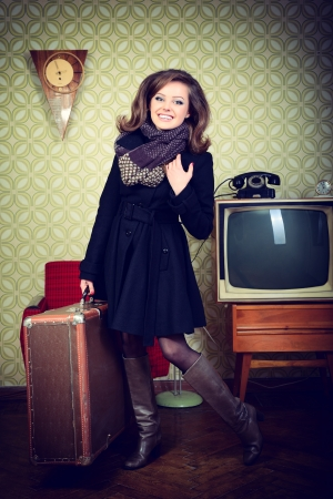 art portrait of young woman holding big suitcase in room with vintage wallpaper and interior with tv, clocks, chair and suitcase, retro stylization 60-70s, toned photo